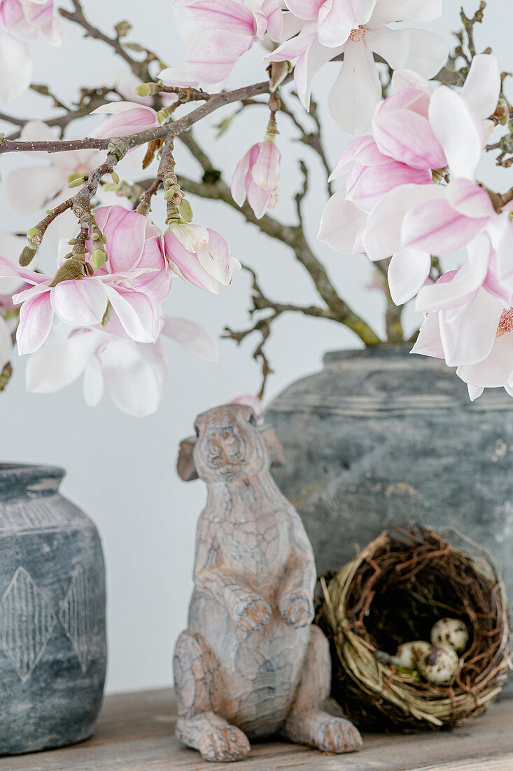 Rabbit figurine and small nest under flowering magnolia branches in vase