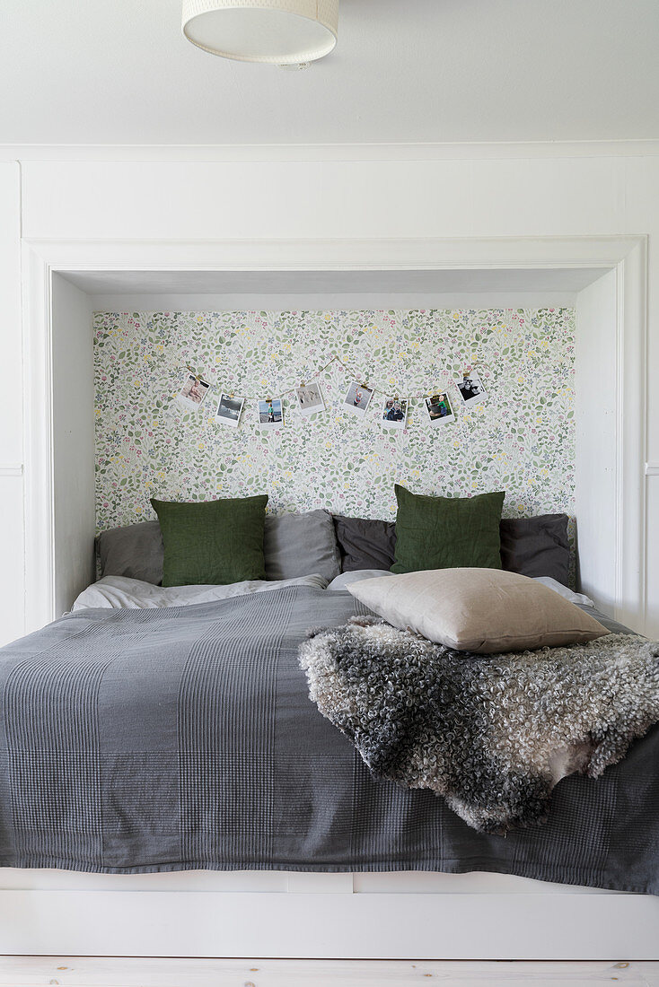 Double bed with head in niche with patterned wallpaper on back wall