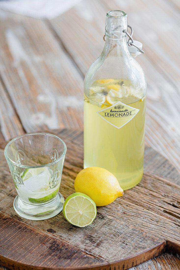 Bottle of lemonade, glass, lemon and lime on wooden board