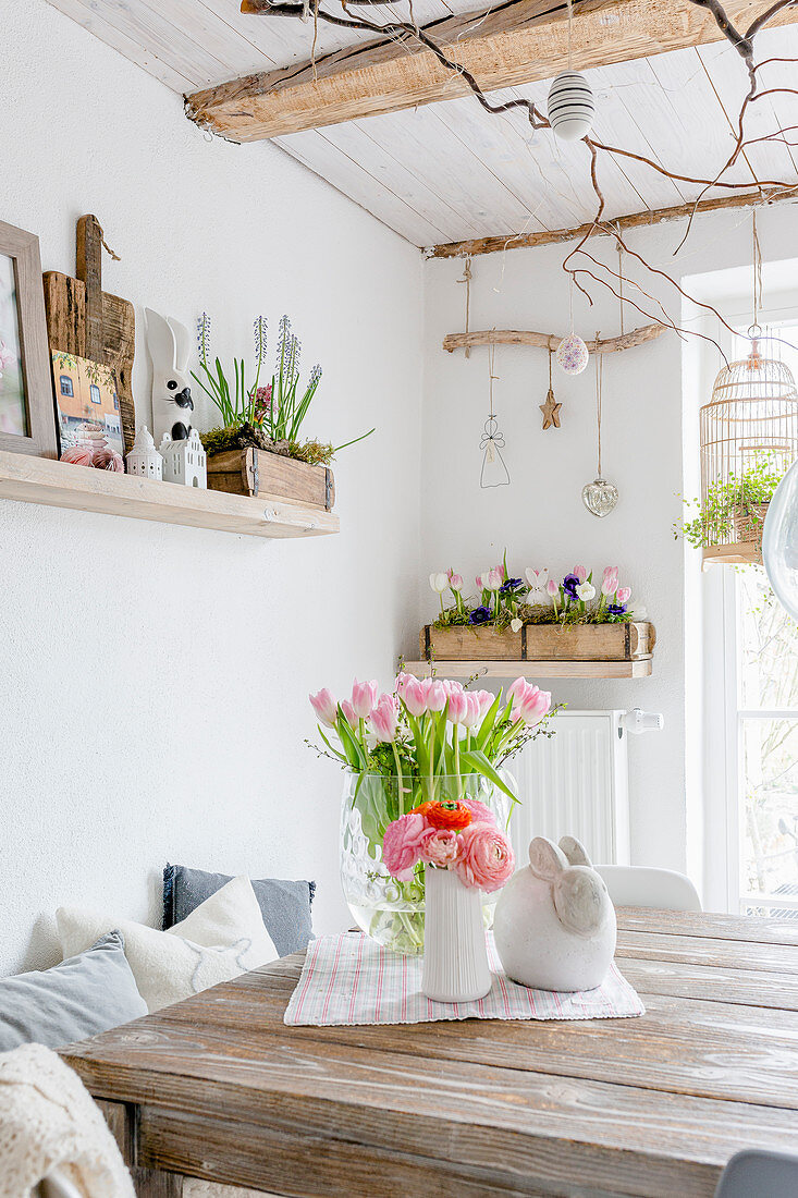 Tulips and ranunculus on wooden table in dining room