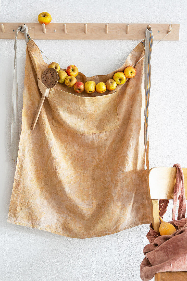 Apron and garland of apples hanging from coat pegs