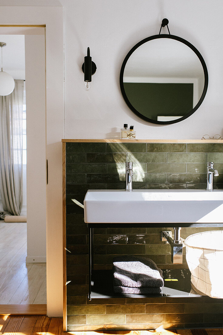 Long sink against green wall tiles with wooden frame