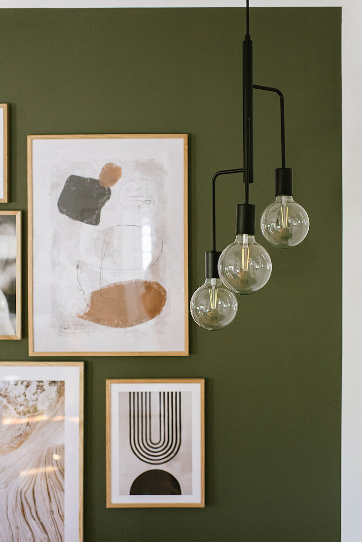 Pendant lamp in front of modern arrangement of pictures on green wall