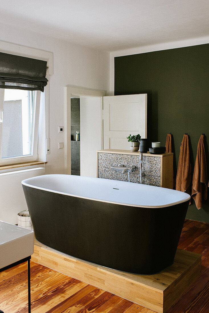 Free-standing bathtub on wooden platform in comfortable bathroom