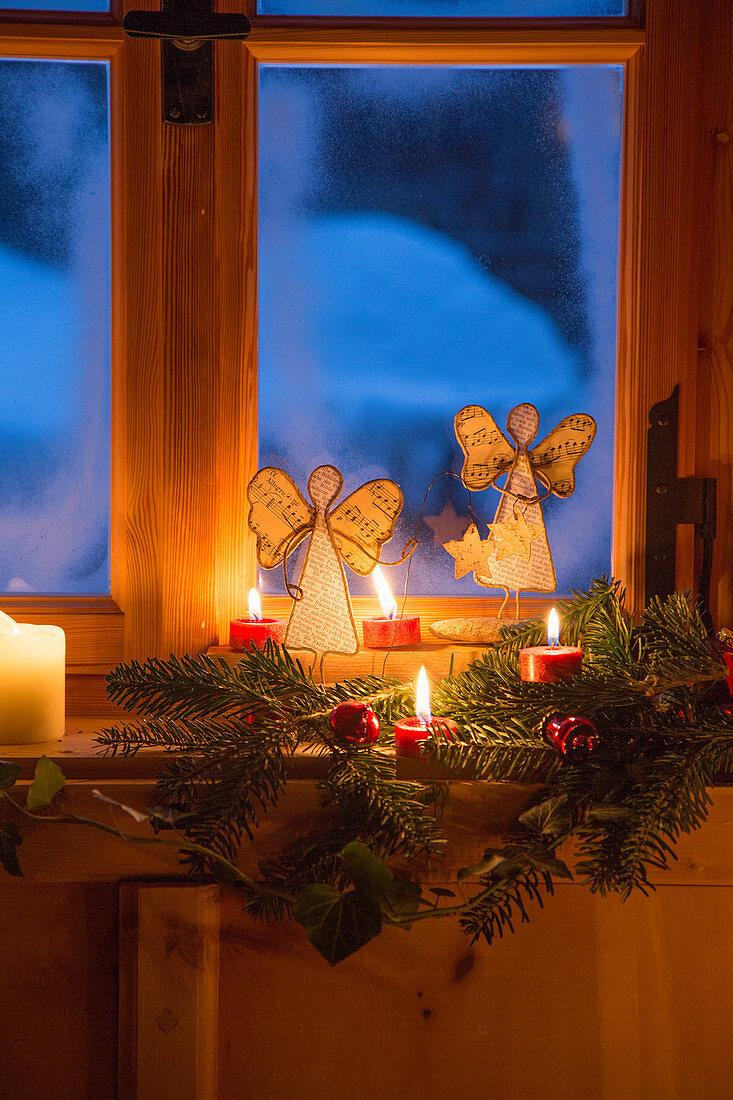 Engel aus Notenpapier und Kerzendeko am ländlichen Fenster