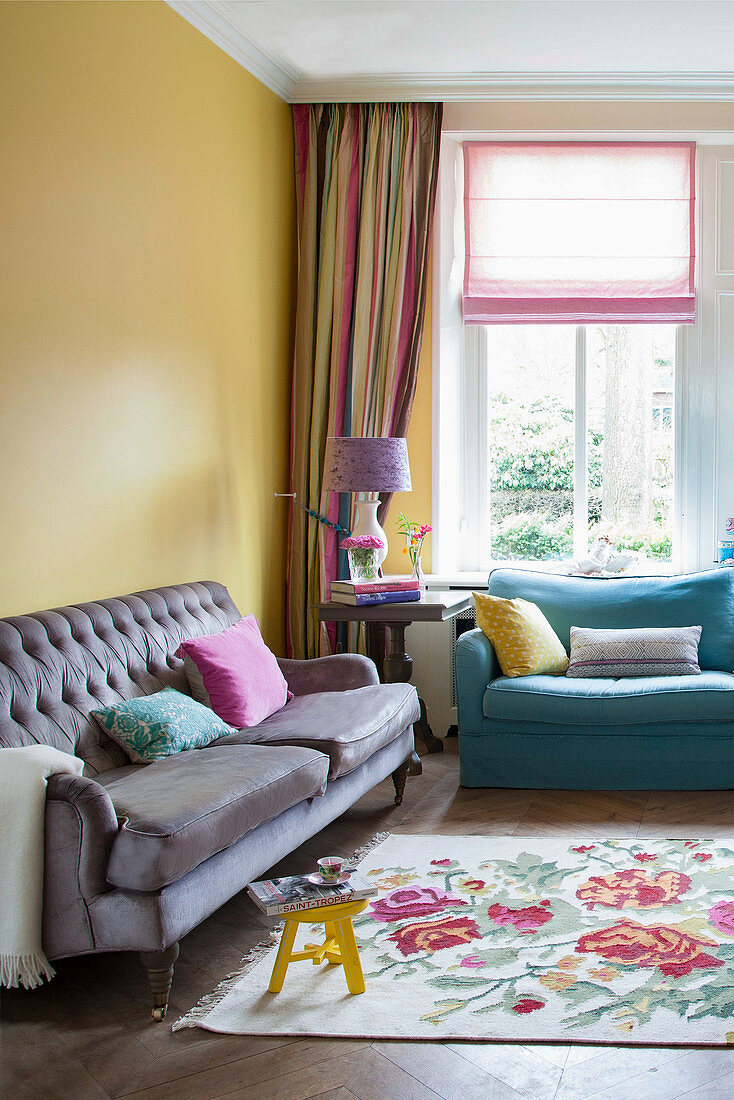 Comfortable sofa and floral rug in living room with yellow walls