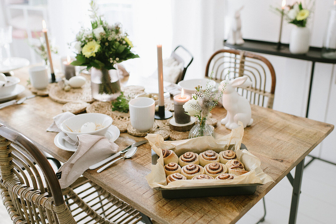 A tray on buns on a table laid for an Easter meal