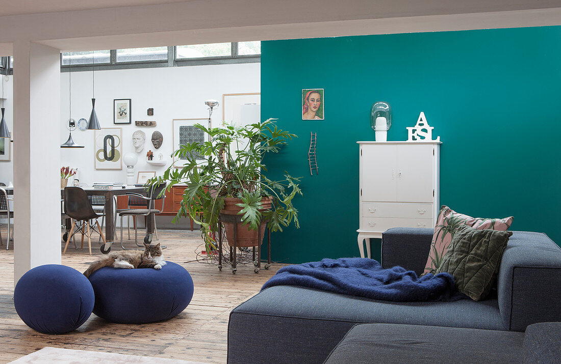 A grey upholstered suite in a lounge area with a turquoise blue wall