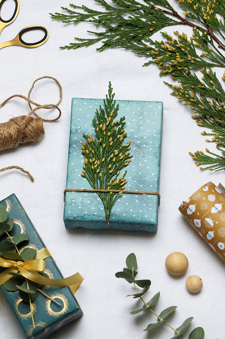 Festively wrapped gift decorated with thuja twig