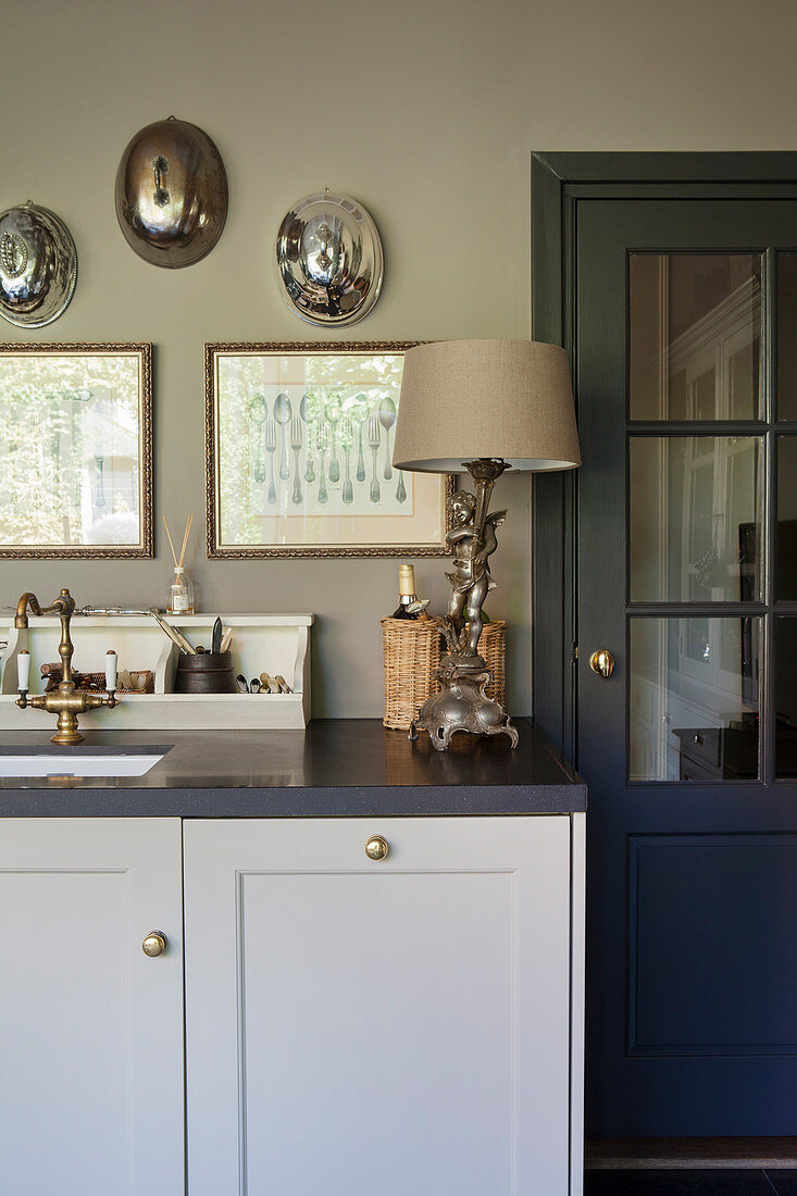 A table lamp with an angel stand next to the sink in a classic grey kitchen