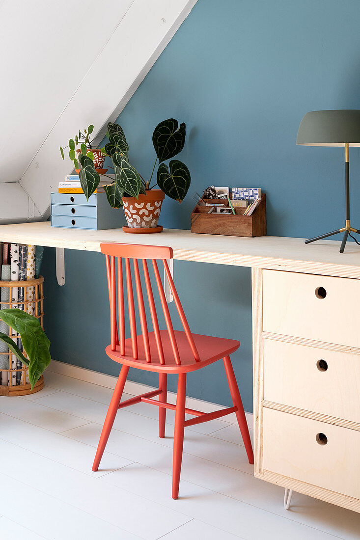Spoke-back chair painted coral red at desk against blue wall
