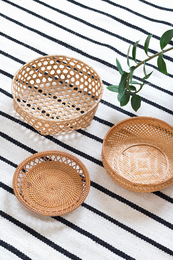 Three baskets on black-and-white striped rug