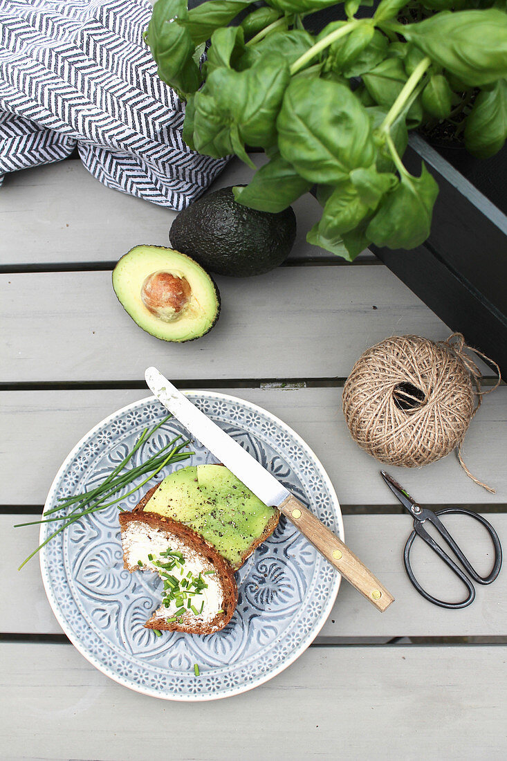 Snack of bread, avocado and chives in garden