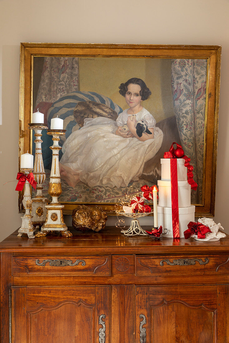 Christmas decorations and Baroque candlesticks in front of portrait of child