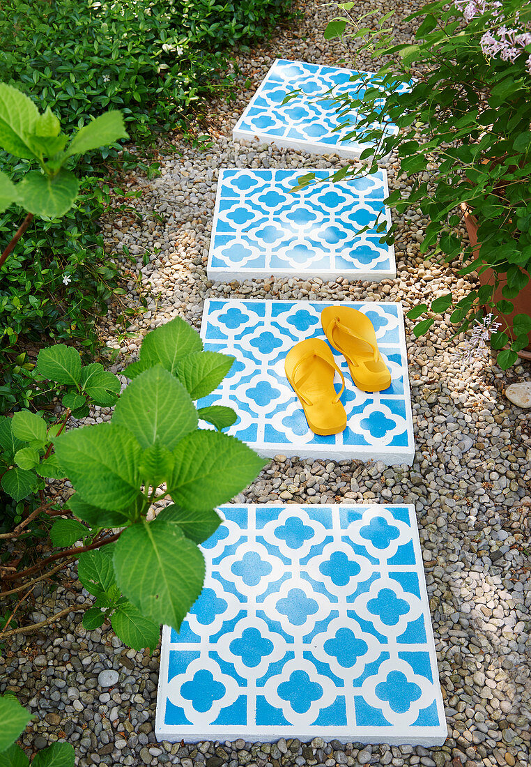 Concrete tiles with ornate pattern used as stepping stones in garden