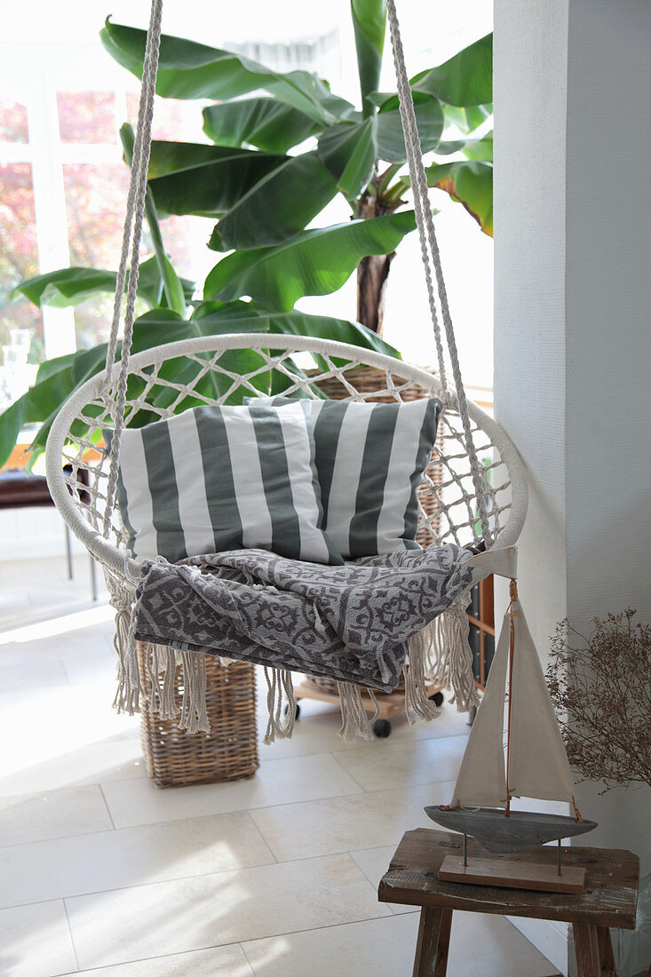 Boat ornament in front of hanging chair with scatter cushions