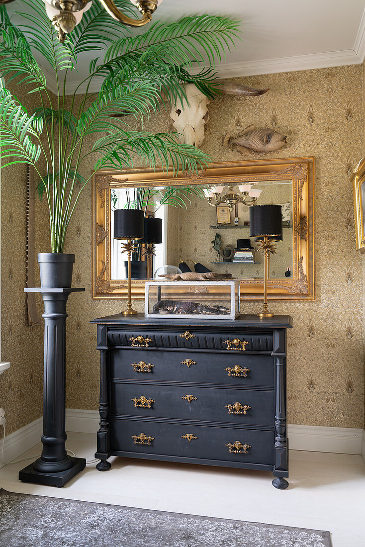 An indoor palm tree on a stela, an antique chest of drawers and a gold-framed mirror on a papered wall