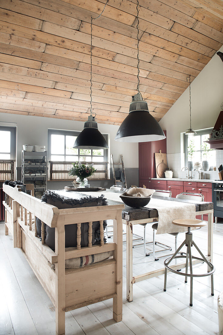 Pendant lights above a dining table with a wooden bench in an open-plan living room