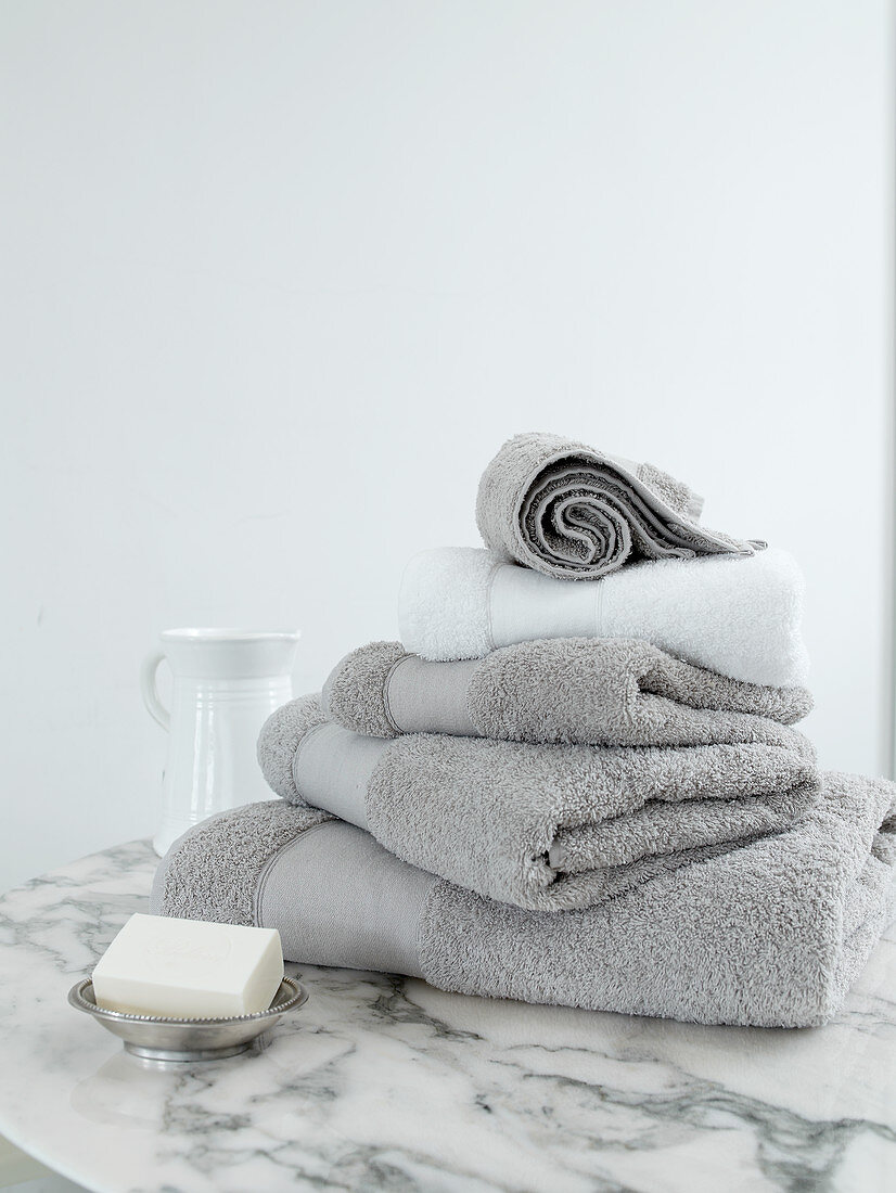 Stack of pale grey towels on marble table against white wall