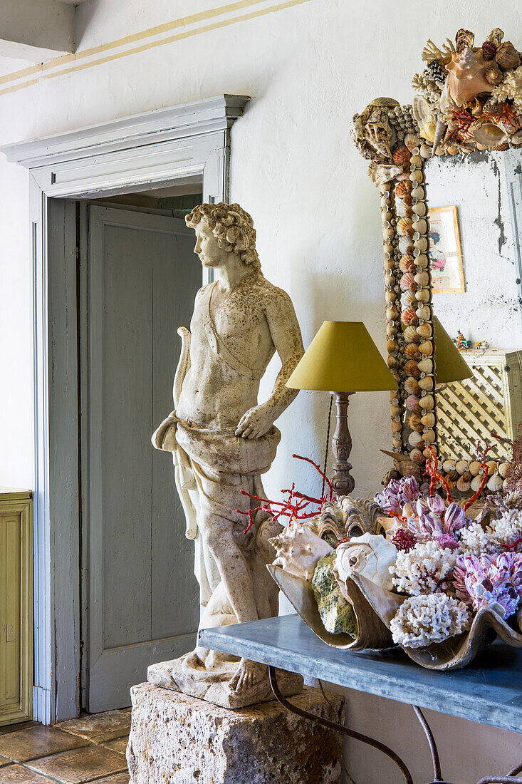 Console table with maritime decoration, wall mirror and statue next to passageway