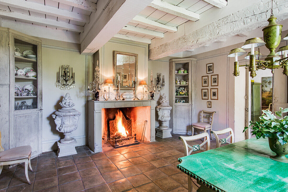 Table with green glazed ceramic top in dining room, fireplace with fire in background