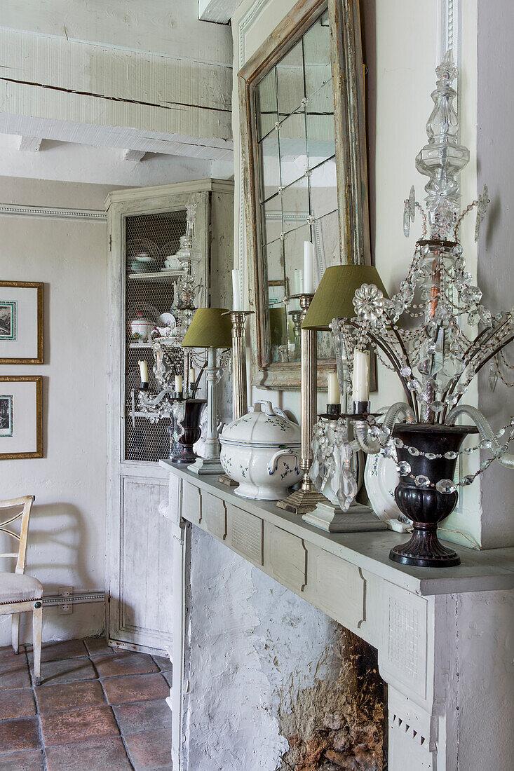 Kaminsims mit Kronleuchter, Tischlampe und Kerzenständer, darüber Spiegel