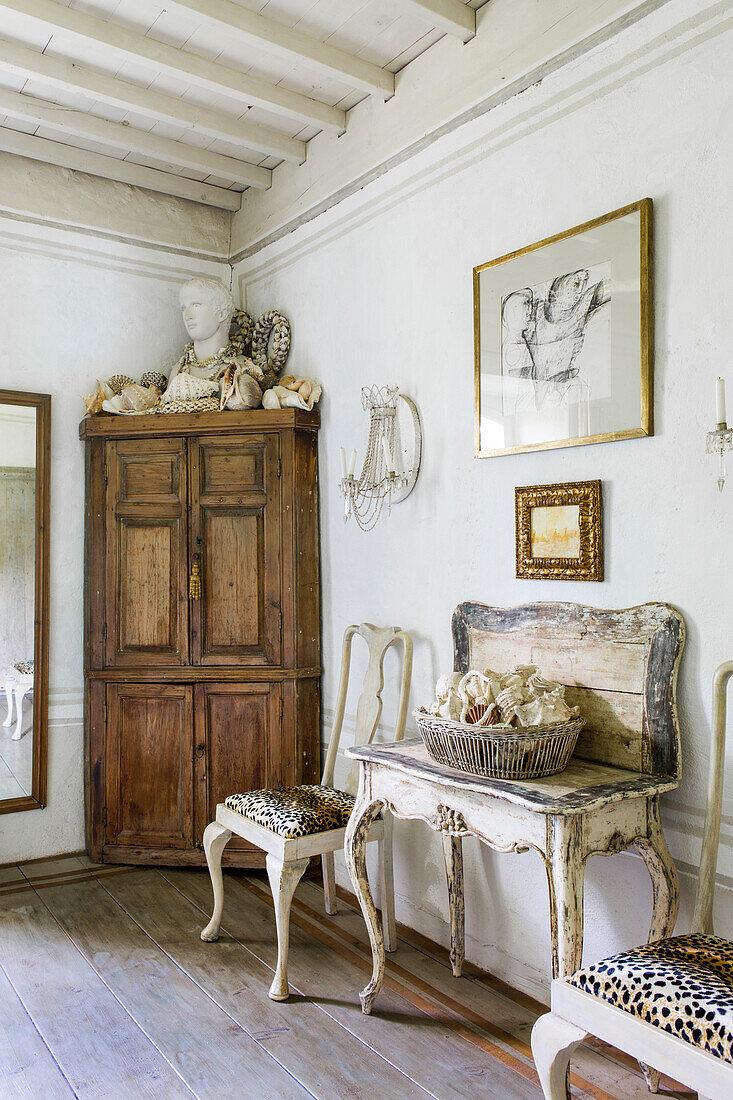 Muschelsammlung auf antikem Holztisch, Stühle und Eckschrank mit Büste im Badezimmer