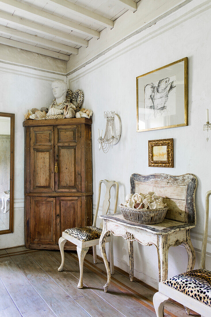 Shell collection on antique wooden table, chairs and corner cabinet with bust in bathroom