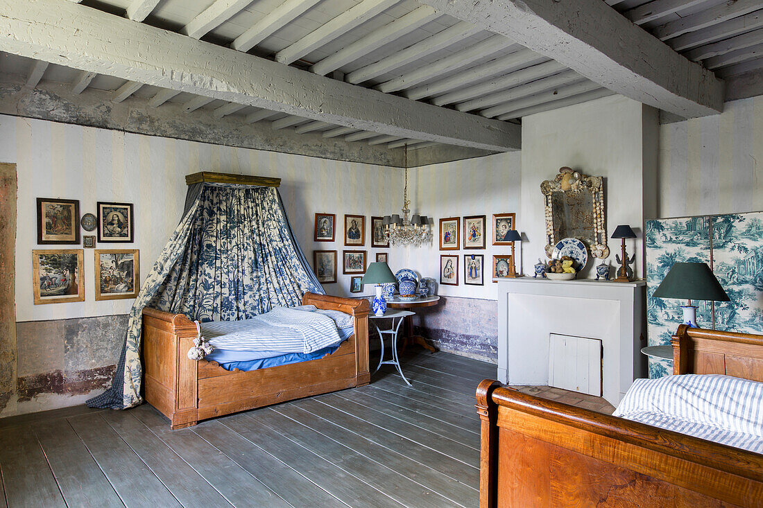 Wooden bed with canopy in Toile de Jouy in guest room