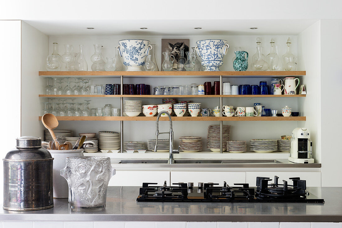 Crockery and glassware storage in kitchen of atelier with five ring hob