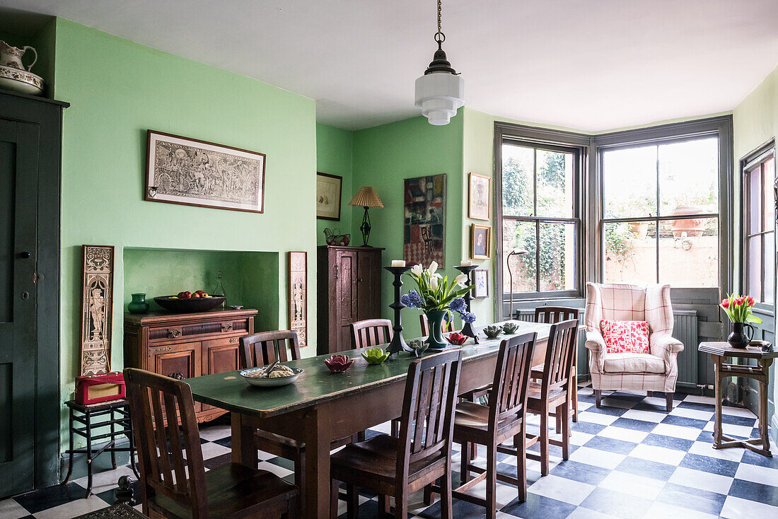 Wooden table and chairs on checkerboard tiles in dining room