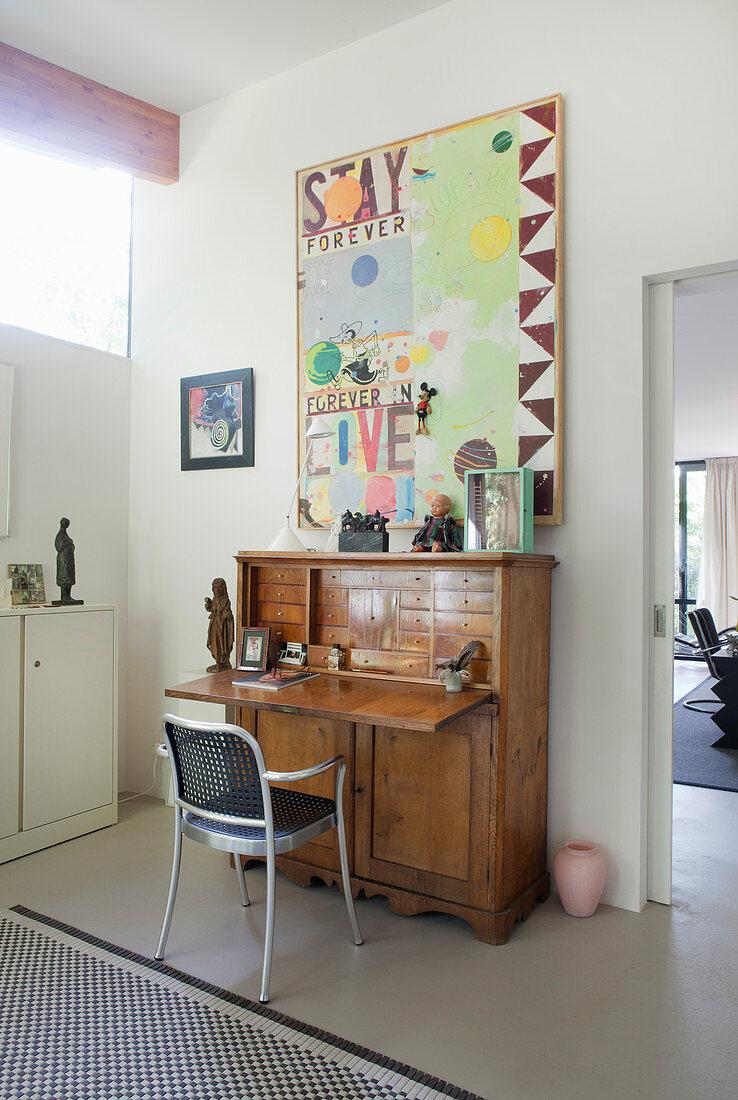 Metal chair at antíque bureau below modern painting