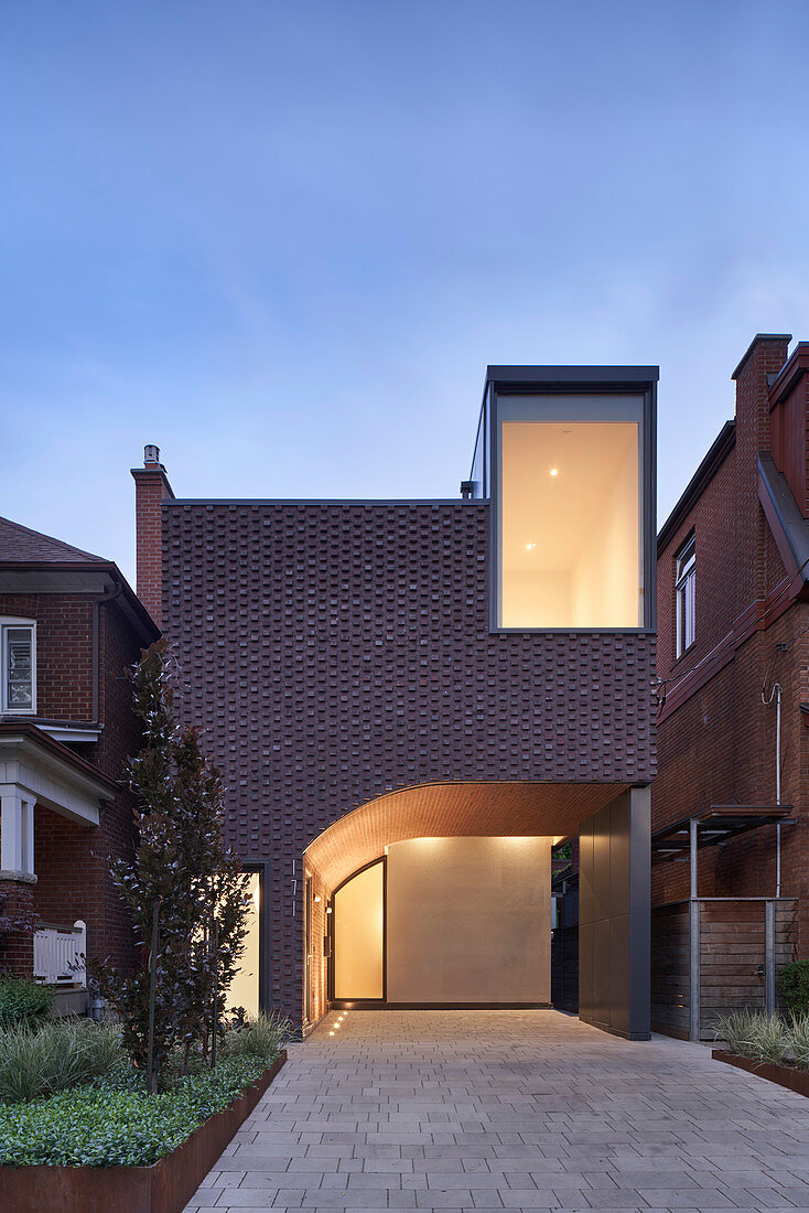 Modern brick house with integrated carport at twilight