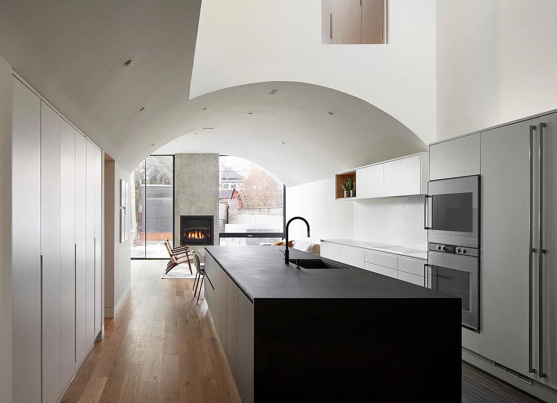 Moderne offene Küche mit Kücheninsel und Gewölbedecke