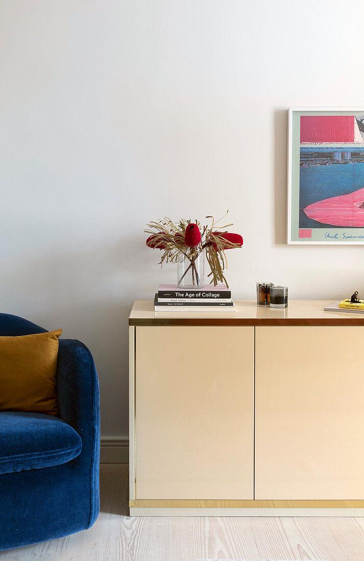 Blue velvet armchair next to beige sideboard