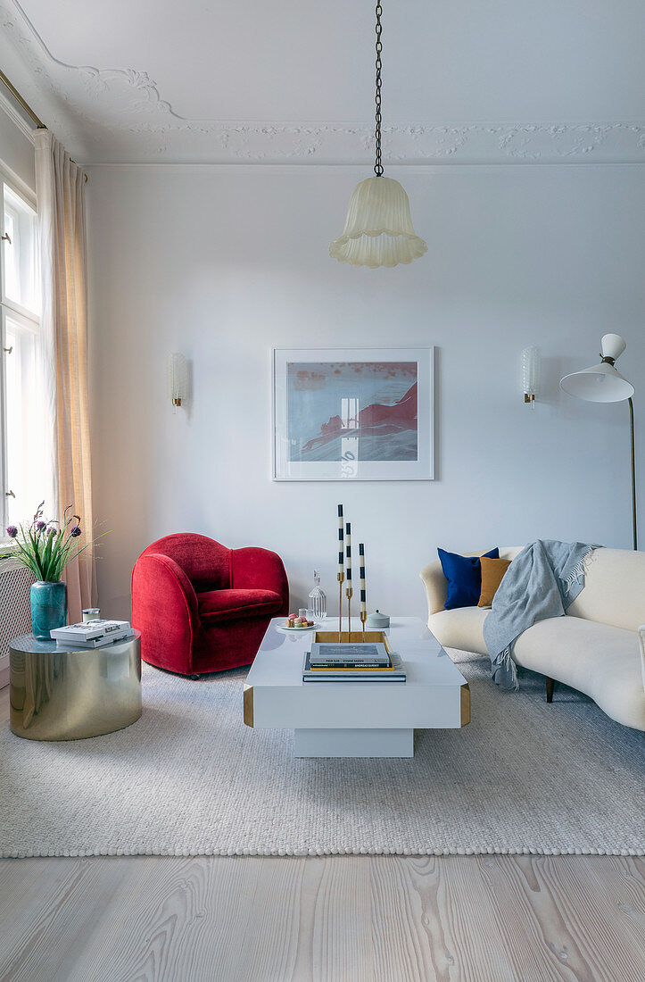 Red armchair, golden side table and beige sofa in living room