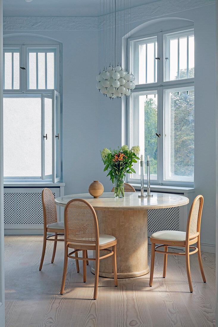 Stühle mit Geflecht am runden Holztisch im Altbau mit Bogenfenster