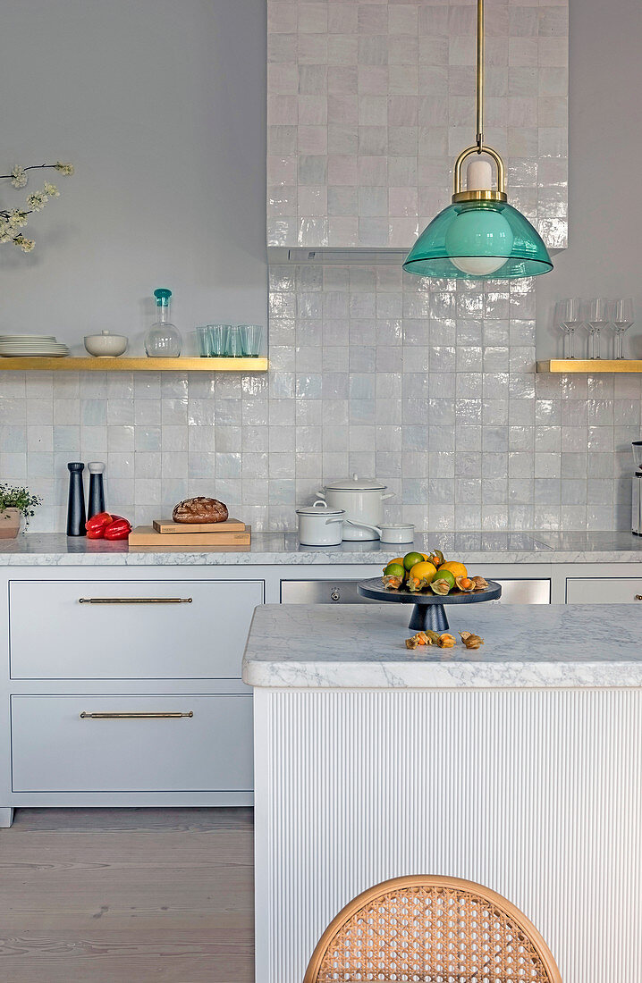 Island counter with marble top in white kitchen with glazed tiles