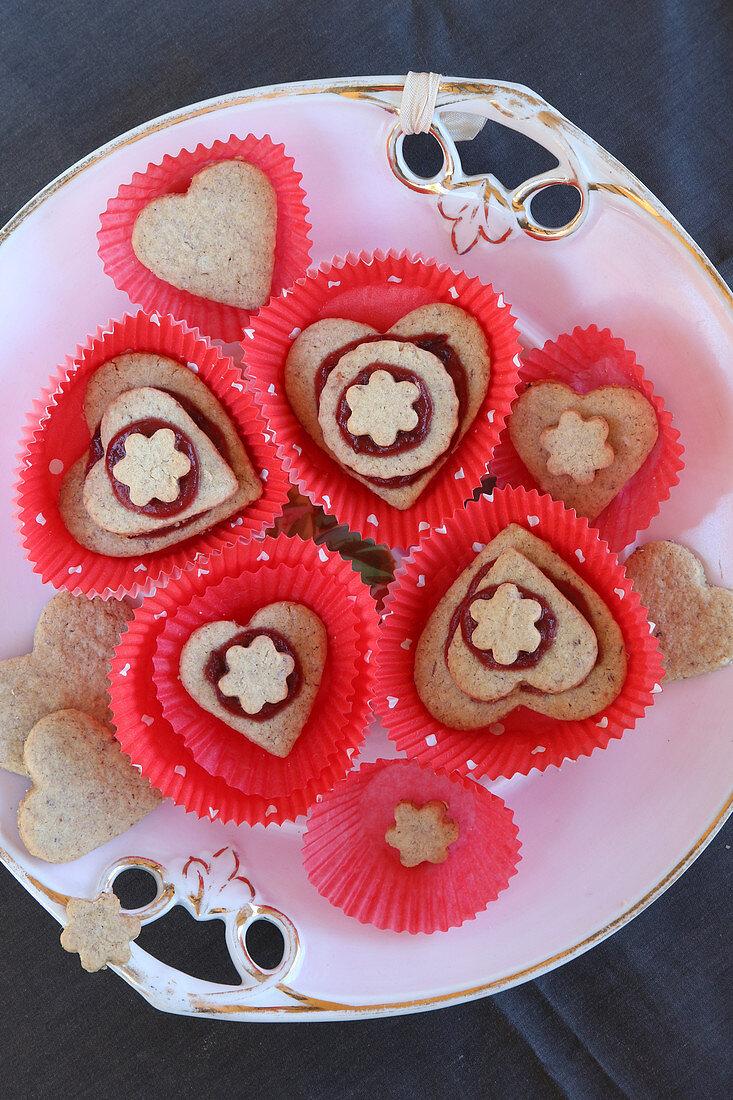 Herzförmige Plätzchen mit Marmelade in roten Muffinförmchen