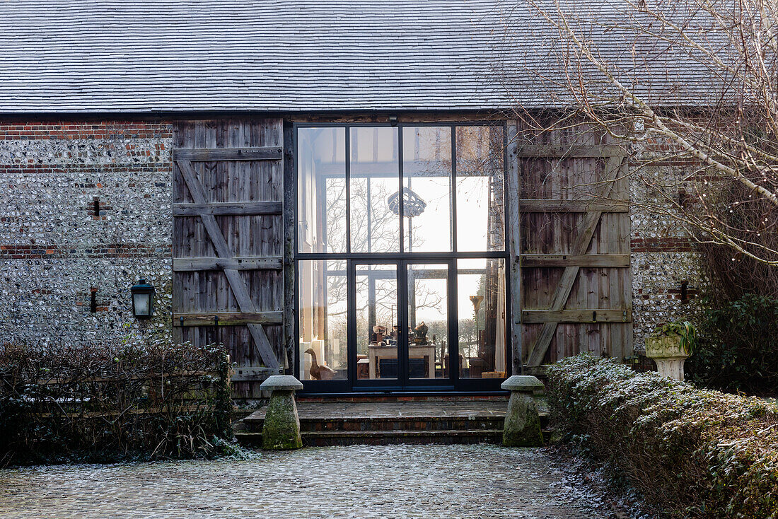 Vast glass doors and timber shutters at exterior of barn conversion