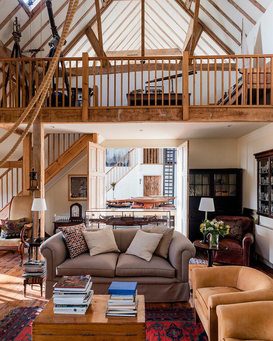 Wildledersessel, Sofa und antike Teleskopen im Wohnzimmer einer renovierten Scheuen mit doppelter Raumhöhe