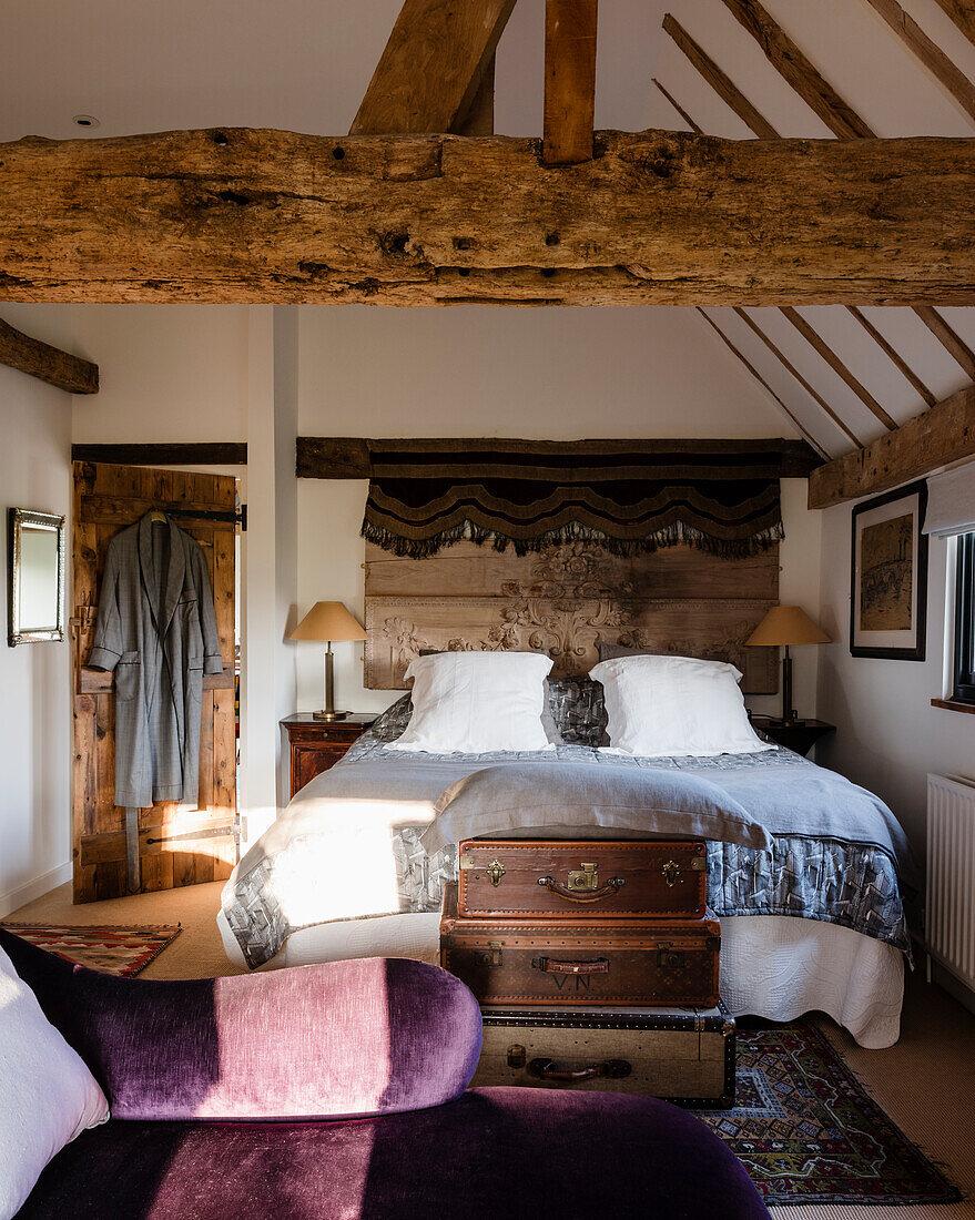 Antike Koffer mit viktoranischer Chaiselongue im Schlafzimmer mit Holzbalken