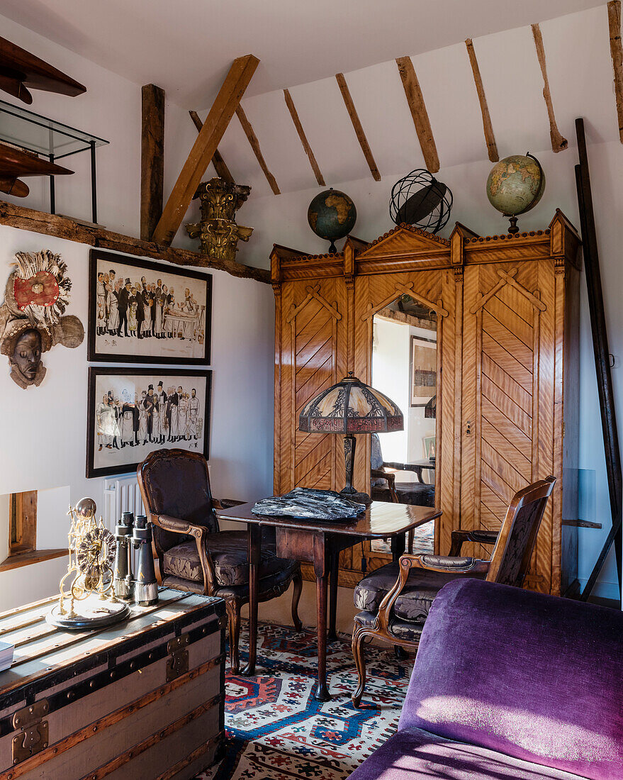 German cupboard topped with several 18th and 19th century globes, an early Caucasian kilim softens the floor, writing table