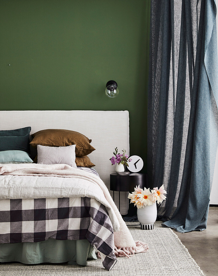Doppelbett mit gepolstertem Kopfteil vor grüner Wand