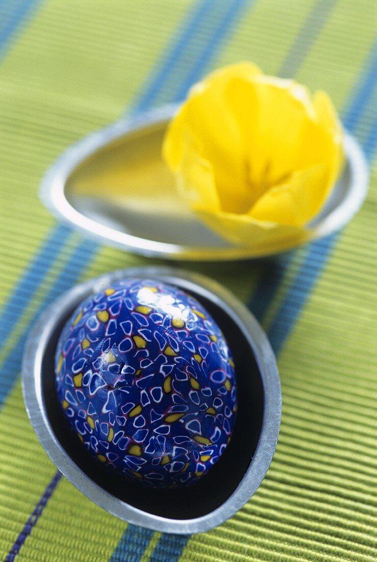 Blaues Osterei und gelbe Tulpenblüte in eiförmigen Schalen