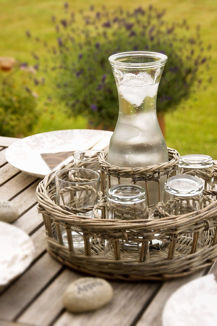 A carafe of water and glass on a tray on a garden table