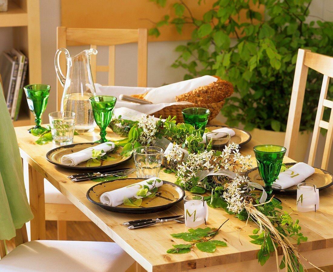 Gedeckter Tisch dekoriert mit Girlande aus Felsenbirne