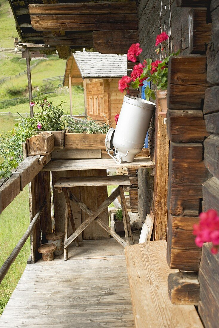 A empty milk can upside down on wooden table outside an Alpine chalet