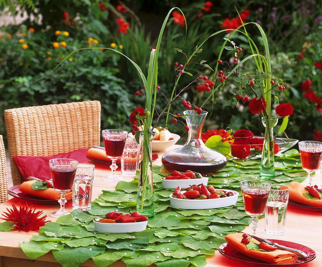 Table decoration: pipevine leaves, peppers and dahlias