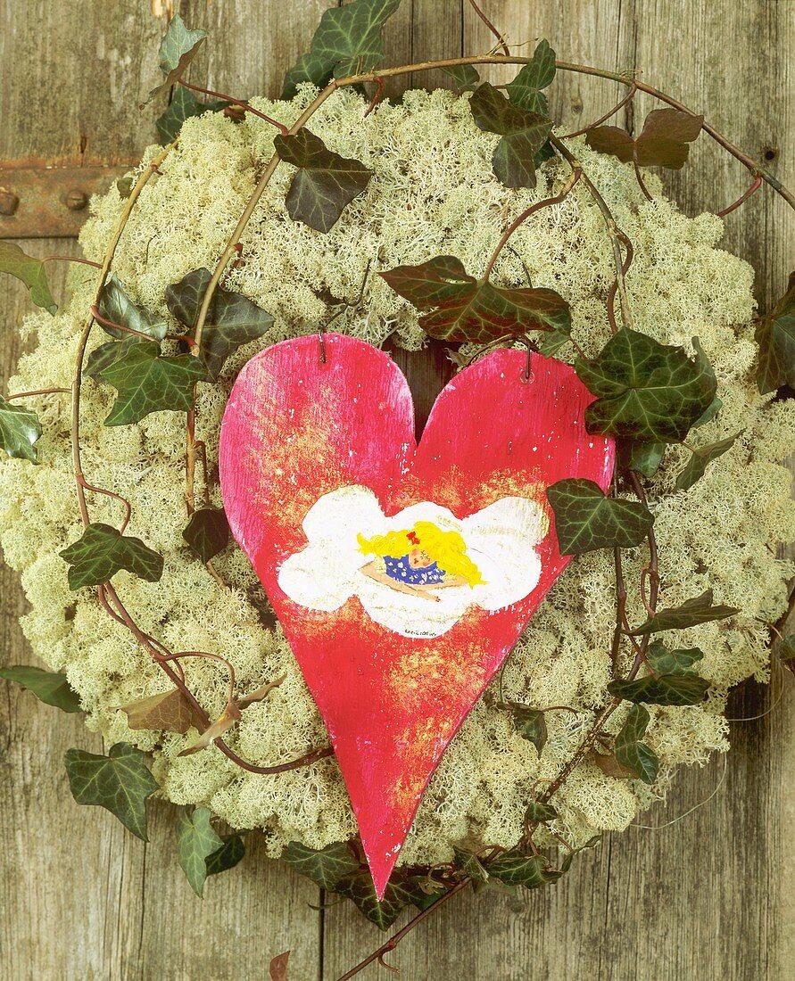 Door wreath of Iceland moss, ivy and red wooden heart